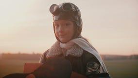 Fantastiskt ståendeskott av lilla flickan i rolig plan pilot- dräkt som ler på kameran med blyg fridsam ögonultrarapid lager videofilmer