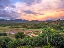Fantastiskt tropiskt landskap med fältet och berget på solnedgången med underbar sagahimmel arkivbilder
