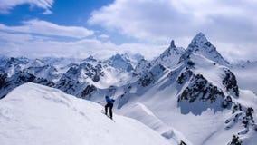 Fantastiskt vinterberglandskap med en manlig glesbygdsområdeskidåkare i förgrunden royaltyfri foto