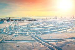 Fantastiskt vinterlandskap med den färgrika solnedgången och den snöig vägen, Hargita berg, Carpathians, Transylvania, Rumänien,  royaltyfri bild