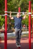 Fantastyczny młody człowiek robi Ups na crossbars na zamazanym tle Siły pojęcie fotografia royalty free