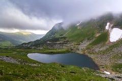 Fantastyczny szeroki pokojowy widok błękitny jezioro w zielonej dolinie i małych turystycznych namiotach przy skalistą górą z łat obrazy stock
