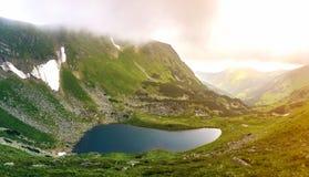 Fantastyczny szeroki pokojowy widok błękitny jezioro w zielonej dolinie i małych turystycznych namiotach przy skalistą górą z łat obraz stock