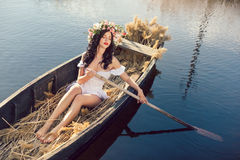 Fantasy art photo of a beautiful girl sitting in boat. Young sexy woman sailing on boat at sunset. The girl has a flower wreath on her head, relaxing and seiling Royalty Free Stock Photos