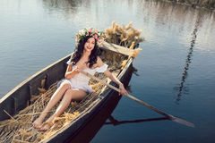Fantasy art photo of a beautiful girl sitting in boat. Young sexy woman sailing on boat at sunset. The girl has a flower wreath on her head, relaxing and sailing Royalty Free Stock Photo