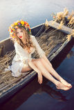 Fantasy art photo of a beautiful lady in boat. Young sexy woman on boat at sunset. The girl has a flower wreath on her head, relaxing on river. Beautiful body Stock Images