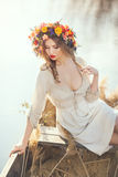 Fantasy art photo of a beautiful lady in boat. Young sexy woman on boat at sunset. The girl has a flower wreath on her head, relaxing on river. Beautiful body Royalty Free Stock Photography