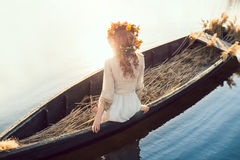 Fantasy art photo of a beautiful lady lying in boat. Young sexy woman on boat at sunset. The girl has a flower wreath on her head, relaxing and seiling on river Royalty Free Stock Photos