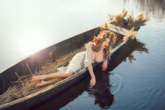 Fantasy art photo of a beautiful lady lying in boat. Young sexy woman on boat at sunset. The girl has a flower wreath on her head, relaxing and seiling on river Royalty Free Stock Image