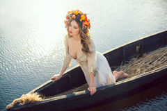 Fantasy art photo of a beautiful lady lying in boat. Young sexy woman on boat at sunset. The girl has a flower wreath on her head, relaxing and seiling on river Royalty Free Stock Images