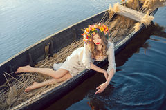 Fantasy art photo of a beautiful lady lying in boat. Young sexy woman on boat at sunset. The girl has a flower wreath on her head, relaxing and sailing on river Stock Photo