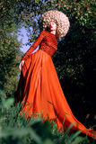 Fantasy. Artistic Stylized Woman in Trendy Red Dress and Big Frizzy Wig Stock Photo