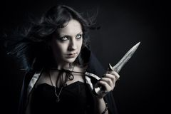 Fantasy assassin. Pretty girl with dagger posing over dark background stock image
