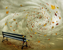 Fantasy bench in autumn. Park bench with autumn leaves flying in a whirlwind Royalty Free Stock Photo