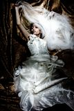 Fantasy bride. Floating on golden dark background royalty free stock image