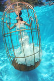Fantasy bride underwater in a bird cage Royalty Free Stock Images