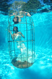 Fantasy bride underwater in a bird cage Stock Photos