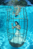 Fantasy bride underwater in a bird cage Royalty Free Stock Photo