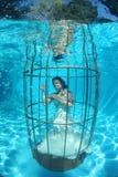 Fantasy bride underwater in a bird cage Royalty Free Stock Photo