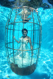 Fantasy bride underwater in a bird cage Royalty Free Stock Image