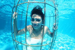 Fantasy bride underwater in a bird cage Stock Photo
