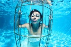 Fantasy bride underwater in a bird cage Stock Image
