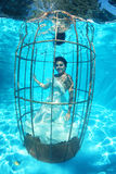 Fantasy bride underwater in a bird cage Stock Image