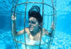 Fantasy bride underwater in a bird cage Stock Photo