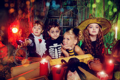 Fantasy children. Group of funny children dressed in halloween costumes in a wizarding lair. Halloween party stock image