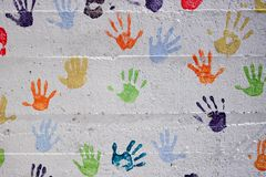 Small children`s hands printed on a white wall