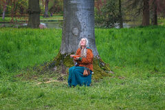 Fantasy figure eating under a tree in the park on the Elf Fantas Royalty Free Stock Photography