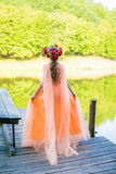 Fantasy girl. With long orange dress and roses crown Stock Photo