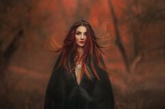 fantasy gothic woman dark witch. Red-haired evil Girl demon in black dress cape hood. Long hair flutters fly in wind