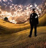 Fantasy Imagining. Man in black suit and bowler hat stands in the field. Clouds in sunset rays. This image created in entirety by me and is entirely owned by me Stock Photos