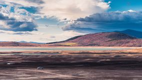 Fantasy landscape with a lonely car. A lonely car parked in the beautiful countryside landscape with vibrant colors in a cloudy day stock images
