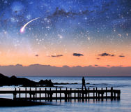 Fantasy landscape - silhouette of a woman walking on pier admiri. Ng stars in the sky. Elements of this image are furnished by NASA Stock Photo