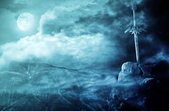 Fantasy landscape and sword. Fantasy sword in dark landscape with moon Royalty Free Stock Photos