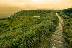 Fantasy-like landscape and path of stepping stones over a grassy bald on Taiwan`s mountainous east coast. Inviting foothpath through a scenic landscape on the Stock Photo