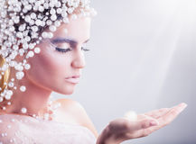 Fantasy make-up. Portrait of beautiful woman with fantasy make-up with hair of white pearls on a light background stock photos