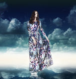 fantasy Mulher luxuoso no vestido Variegated sobre o céu azul fotografia de stock royalty free