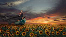 Fantasy portrait of young woman in black dress on the boat. Fantasy portrait of young magnificent woman in long black dress flying on boat over sunflowers field Stock Photos