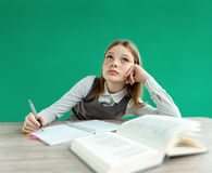Fantasy pupil looking up as if daydreaming or thinking of something, while sitting at the desk with open book. Stock Image