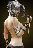 Fantasy rouge warrior female posing semi nude with helmet and dagger. Royalty Free Stock Photography