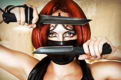 Fantasy style - girl with creative make up. Fantasy style - red haired woman with dark creative make up, mask on her face and two combat knifes Royalty Free Stock Images