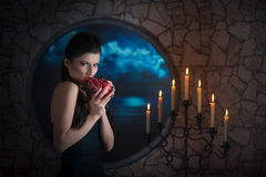 Demonic woman with a pomegranate. Fantasy style portrait of demonic woman biting a pomegranate Royalty Free Stock Images