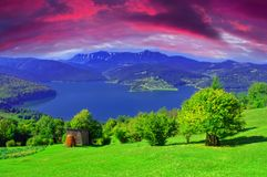 Fantasy summer landscape with Carpathian mountain and lake, sunset clouds added. Romania stock photo