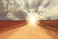 Fantasy Sunrise Sunset at the end of Dirt Road - Horizon. In the open wilderness at the end of a long dirt road, the sun magically breaks over the horizon royalty free stock photos