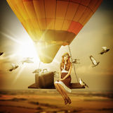 Fantasy travel. Young woman flying a balloon stock photography