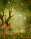 Fantasy tree by a pond. Fantasy tree with lanterns by the pond and meadow with red flowers Stock Photo