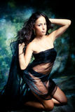 Fantasy woman. Brunette woman in black on fantasy background Royalty Free Stock Photography
